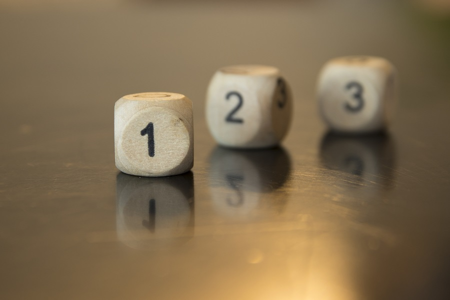 Rolling three dice on a wooden desk. Rolling the dice concept fo
