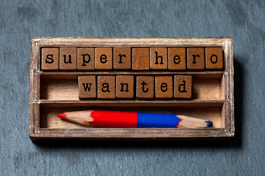 Super hero wanted phrase. Recruiting and personal searching concept quote. Vintage box, wooden cubes with old style letters, red blue pencil. Gray textured background. Close-up, up view, soft focus